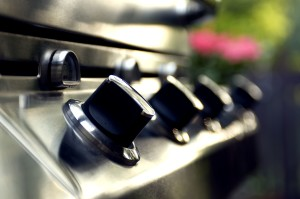 A closeup of knobs on a stainless steel outdoor range top.