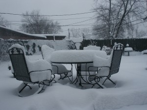 Patio furniture covered in snow.